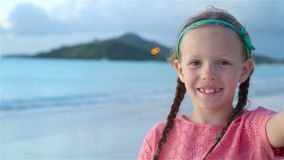 Adorable little girl taking selfie at tropical white beach. SLOW MOTION. Adorable little girl making selfie at tropical white beach stock video footage
