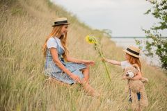 Mother and daughter with sunflowers. Adorable little girl with teddy bear presenting sunflowers to happy mother on meadow stock photography
