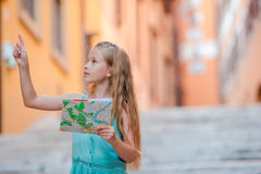 Adorable little girl with touristic map in roman streets in Italy. Happy toodler kid enjoy italian vacation holiday in. Young beautiful girl on steps with city Stock Image