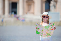 Adorable little girl with touristic map in St. Peter's Basilica square, Italy. Happy toodler kid enjoy italian vacation Stock Photo