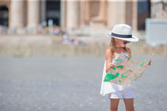 Adorable little girl with touristic map in St. Peter`s Basilica square, Italy. Stock Photo