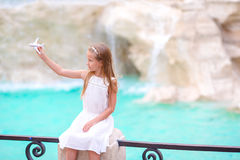 Adorable little girl with toy airplane background Trevi Fountain, Rome, Italy. Happy toodler kid enjoy italian vacation Royalty Free Stock Photos
