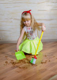 Adorable little girl with a toy broom and pan Royalty Free Stock Photos