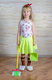 Adorable little girl with a toy broom and pan Royalty Free Stock Photo