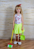 Adorable little girl with a toy broom and pan Royalty Free Stock Photography