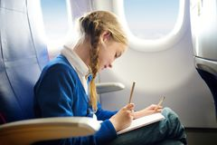 Adorable little girl traveling by an airplane. Child sitting by aircraft window and drawing a picture with colorful pencils. Trave Royalty Free Stock Images