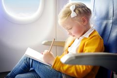 Adorable little girl traveling by an airplane. Child sitting by aircraft window and drawing a picture with colorful pencils. Royalty Free Stock Photography