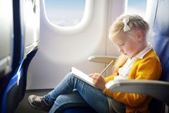 Adorable little girl traveling by an airplane. Child sitting by aircraft window and drawing a picture with colorful pencils. Trave Stock Images