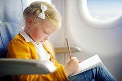 Adorable little girl traveling by an airplane. Child sitting by aircraft window and drawing a picture with colorful pencils. Trave Royalty Free Stock Photography