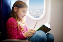 Adorable little girl traveling by an airplane. Child sitting by aircraft window and drawing a picture with colorful pencils. Trave Royalty Free Stock Image