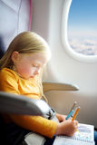 Adorable little girl traveling by an airplane. Child sitting by aircraft window and drawing a picture with felt-tip pens. Royalty Free Stock Image