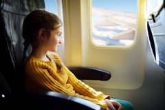 Adorable little girl traveling by an airplane Royalty Free Stock Images