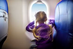 Adorable little girl traveling by an airplane. Child sitting by aircraft window and looking outside. Traveling with kids. Stock Images