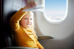 Adorable little girl traveling by an airplane. Child sitting by aircraft window playing with paper plane. Royalty Free Stock Images