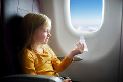 Adorable little girl traveling by an airplane. Child sitting by aircraft window playing with paper plane. Stock Photos