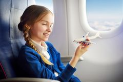 Adorable little girl traveling by an airplane. Child sitting by aircraft window and playing with toy plane. Traveling with kids. Stock Photos