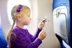 Adorable little girl traveling by an airplane. Child sitting by aircraft window and playing with toy plane. Traveling with kids. Adorable little girl traveling Stock Photography