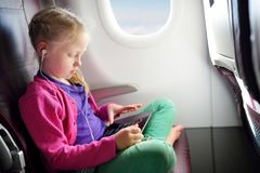 Adorable little girl traveling by an airplane. Child sitting by aircraft window and using a digital tablet during the flight. Traveling abroad with kids royalty free stock image