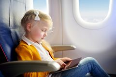 Adorable little girl traveling by an airplane. Child sitting by aircraft window and using a digital tablet during the flight. Trav Stock Photos