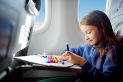 Adorable little girl traveling by an airplane. Child sitting by the window and drawing. Stock Photo