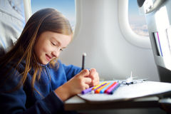 Adorable little girl traveling by an airplane. Child sitting by the window and drawing. Adorable little girl traveling by an airplane. Child sitting by aircraft Stock Image