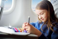 Adorable little girl traveling by an airplane. Child sitting by the window and drawing. Adorable little girl traveling by an airplane. Child sitting by aircraft stock photography