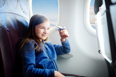 Adorable little girl traveling by an airplane. Child sitting by the window and playing with toy plane. Stock Photos