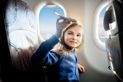 Adorable little girl traveling by an airplane. Child sitting by the window and playing with toy plane. Stock Image