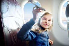 Adorable little girl traveling by an airplane. Child sitting by the window and playing with toy plane. Royalty Free Stock Photos