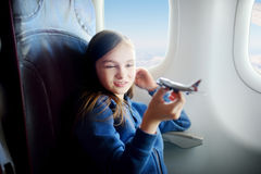 Adorable little girl traveling by an airplane. Child sitting by the window and playing with toy plane. Royalty Free Stock Photo