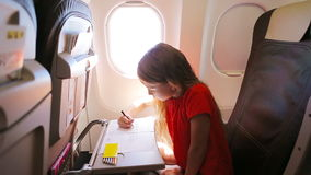 Adorable little girl traveling by an airplane. Kid drawing picture with colorful pencils sitting near aircraft window stock video footage