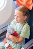 Adorable little girl traveling by an airplane. Kid sitting near aircraft window Royalty Free Stock Image