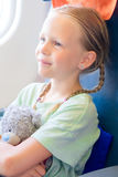 Adorable little girl traveling by an airplane. Kid sitting near aircraft window with teddy bear Royalty Free Stock Images