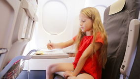 Adorable little girl traveling by plane sitting by aircraft window. Kid drawing picture with colorful pencils. stock footage