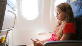 Adorable little girl traveling by plane sitting near window. Kid listening music sitting near aircraft window stock video