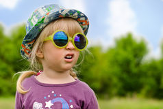 Adorable little girl in trendy sunglasses Stock Images