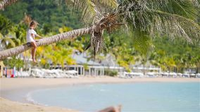 Adorable little girl sitting on palm tree during summer vacation on white beach. Adorable little girl at tropical beach sitting on palm tree during summer stock video footage