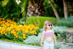 Adorable little girl at the tropical resort, standing by the palm three at the sunny summer day. Adorable little girl wearing sunglasses, walking at the tropical royalty free stock photos