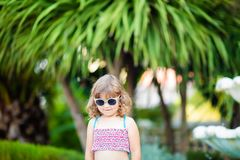 Adorable little girl at the tropical resort, standing by the palm three at the sunny summer day royalty free stock image