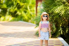 Adorable little girl at the tropical resort, sunny summer day. Adorable little girl at the tropical resort, walking at the hotel territory, palm trees at the royalty free stock photography