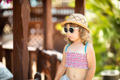 Adorable little girl at the tropical resort, sunny summer day. Adorable little girl at the tropical resort, walking at the hotel territory, palm trees at the stock photo