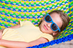 Adorable little girl on tropical vacation relaxing in hammock Stock Photos