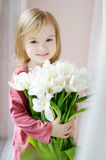 Adorable little girl with tulips by the window stock photography