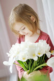 Adorable little girl with tulips by the window Royalty Free Stock Photography