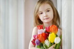 Adorable little girl with tulips by the window Stock Image