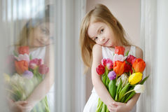Adorable little girl with tulips by the window Stock Photo
