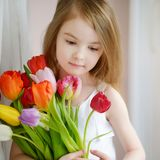 Adorable little girl with tulips by the window Royalty Free Stock Photos
