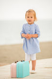 Adorable little girl with two small suitcases royalty free stock photo