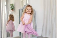 Adorable little girl with umbrella white interior Stock Photo