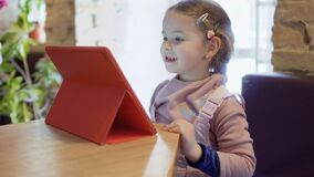 Adorable little girl uses digital tablet in cafe. Cute little girl is sitting in a cafe and uses digital tablet. The girl is watching the cartoons and waits when stock video footage